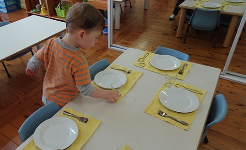 Photo of a child setting the table for a meal.