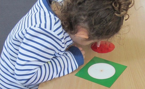 Photo of a student experiencing mathematics with Montessori materials.