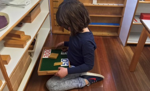 Photo of a student exploring with Montessori materials the Decimal System.