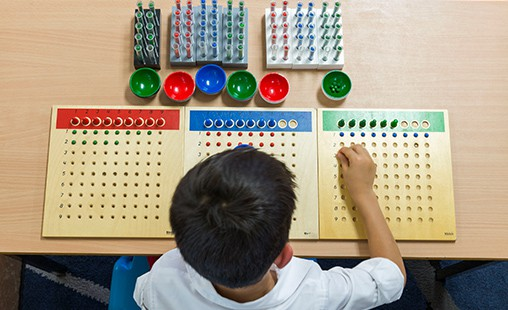 Photo of student performing long division with the racks and tubes materials.