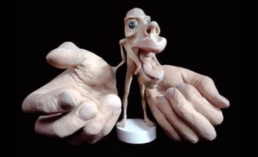 Photo of a sculpture of a small person with large hands.