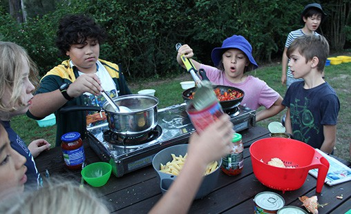 Photo of students cooking out of doors while camping.