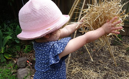 Photo of a child using hay to develop knowledge and skills of every day experiences.